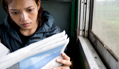 Image of a young woman reading a newspaper.