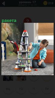 Мальчик в комнате на полу собирает из игрушек ракету