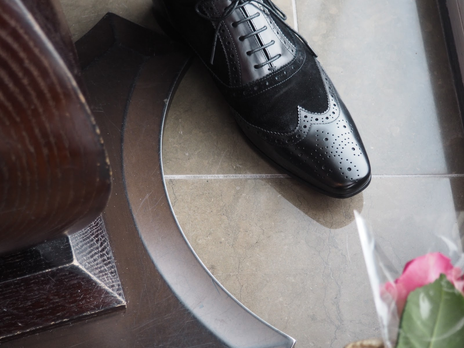 Men's shoes and roses under a table