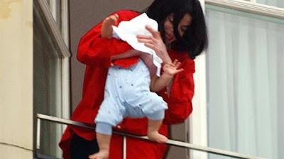el cantante sostiene a su hijo en el balcón de un hotel