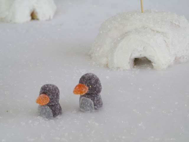 white snow scene with igloos and gumdrop penguins