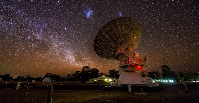 The Large (centre left) and Small (centre right) Magellanic Clouds are seen in the sky above a radio telescope that is part of the Australia Telescope Compact Array at the Paul Wild Observatory in New South Wales, Australia. Image: Mike Salway