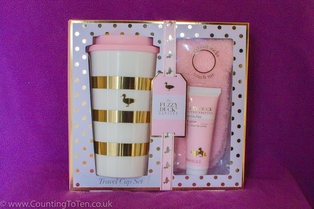 A boxed set of a travel cup, pink fluffy socks and a tube of foot balm