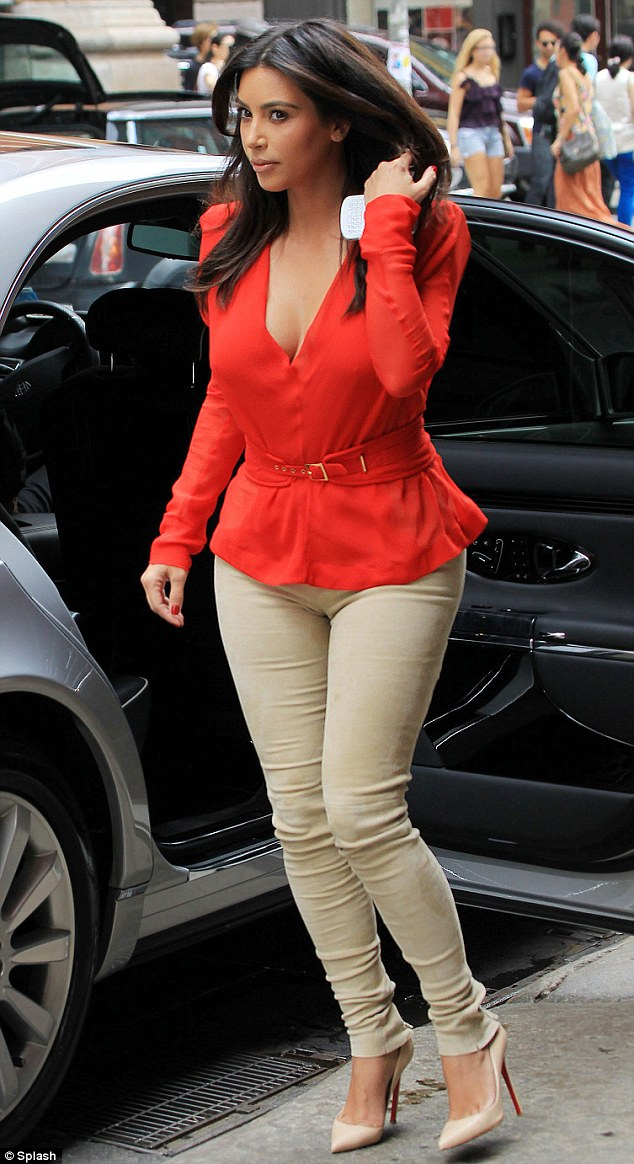 8f74b4ce89d Checking they're still there: Kim looks down at the cleavage as she shows  off her figure in plunging red shirt
