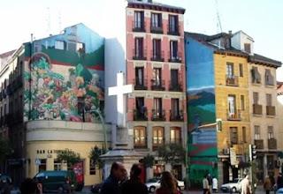 Lateral de la plaza con enormes pinturas en las paredes de sus edificios. En el centro una cruz blanca de piedra.