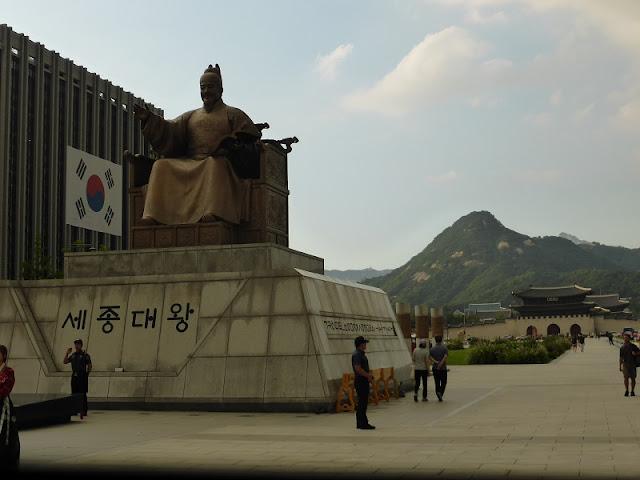Estatua del Rey Sejong El Grande con el palacio y las montañas al fondo
