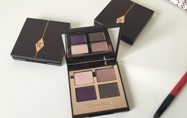 CHARLOTTE TILBURY COLOUR-CODED EYESHADOW in The Glamour Muse, next to two closed Colour-Coded Eyeshadow palettes on a dresser; a brief glimpse of Smashbox's duo eyeshadow brush is just visible in the bottom right corner