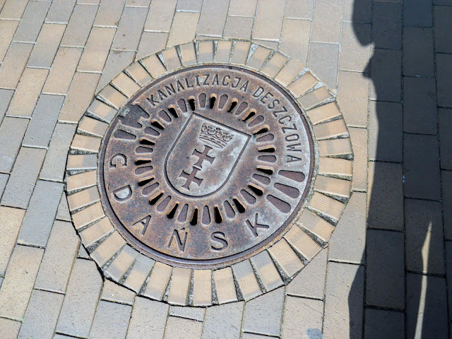 What to see in Tricity Poland: manhole covers with the city name stamped on it in Gdansk