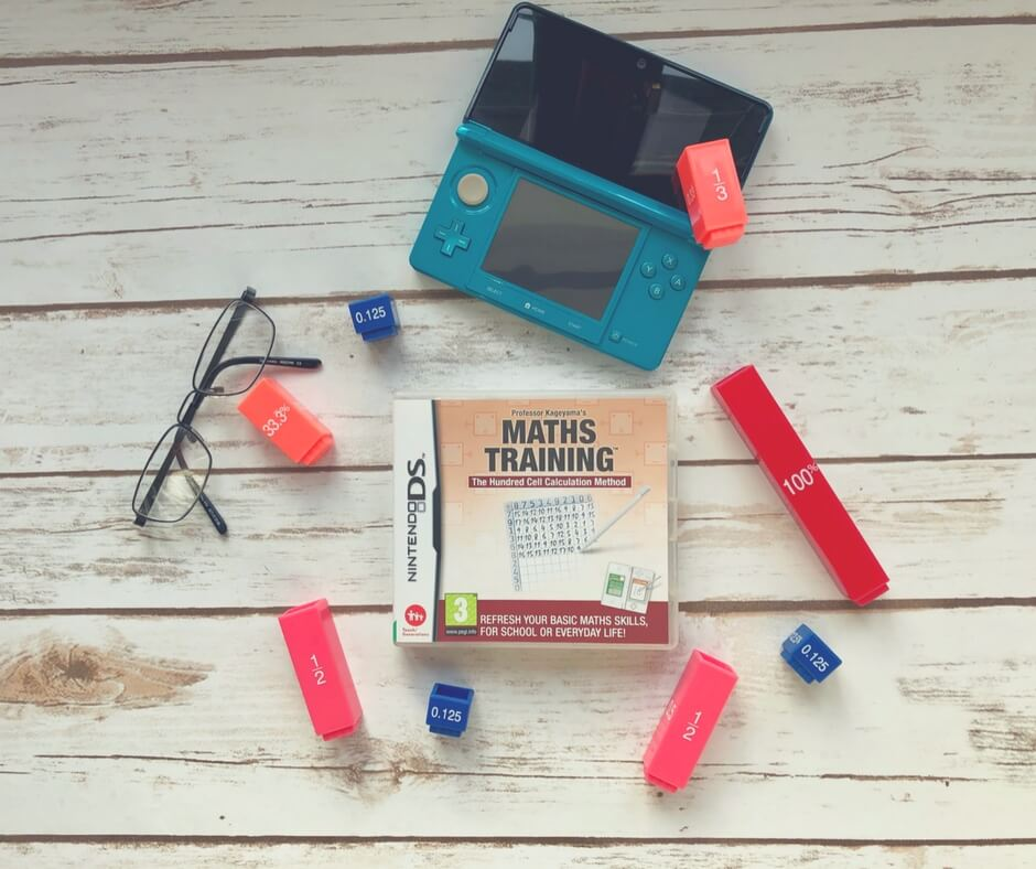 A Nintendo DS game, Maths Training, surrounded by cubes with mathematical equations on them. A 3DS sits above the game and a pair of glasses sit on the table too.