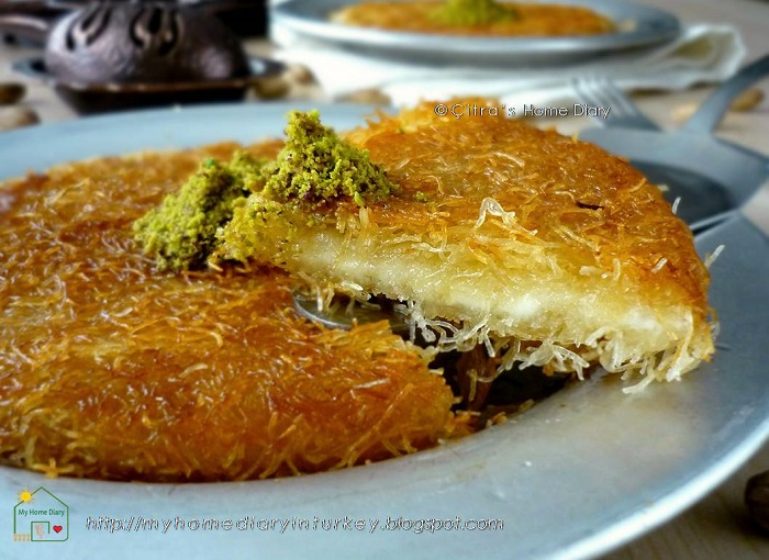 Künefe or kanafeh or kunafeh or kunafah or ... I don't know any other names of it.. But basically it's sweet pastry made from wiry kadaif filled/ layered with unsalty soft cheese and soaked in sugar syrup. Served hot or room temperature.  Künefe is popular from Turkey and from some Mediterranean countries (as a former Ottoman Empire).
