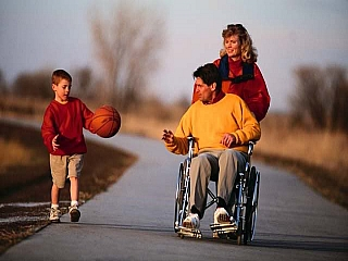 A disabled father in a wheelchair with his family