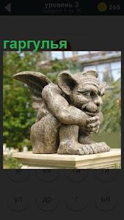 Скульптура на постаменте гаргулья в сидячем положении с крыльями за спиной