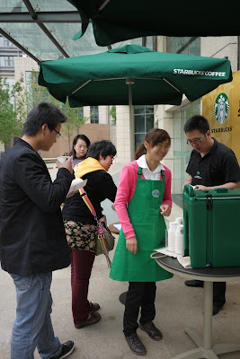 several Chinese people being offered sample drinks