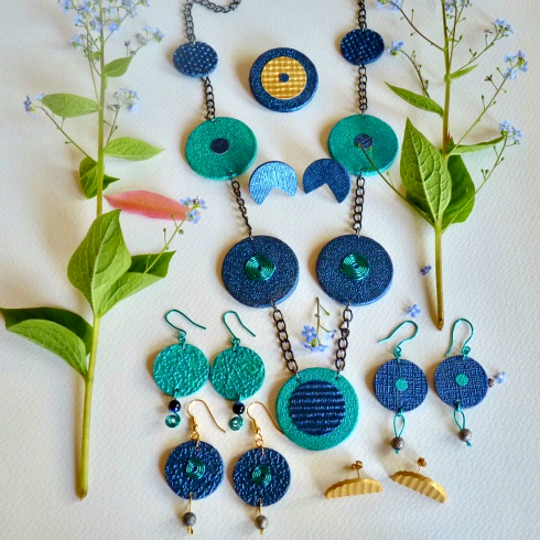 Mixed media circular earrings and necklace in shades of blue, gold, and turquoise