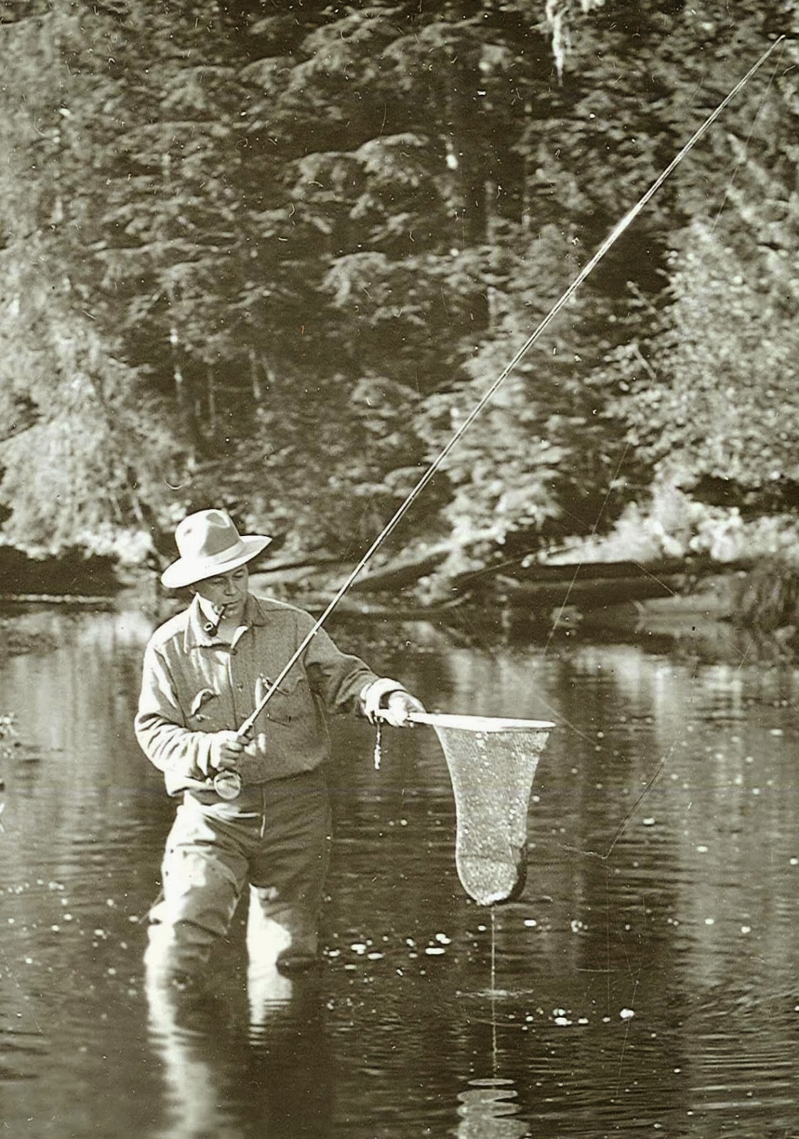 A black and white photograph of a man fishing.