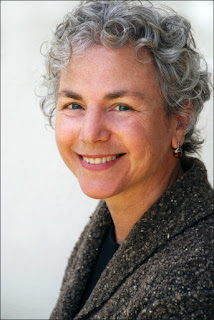 Image of Ellen Bass wearing a brown, gray, and white boucle wool sweater. She smiles at the camera. She has short, gray, curly hair, and blue eyes.