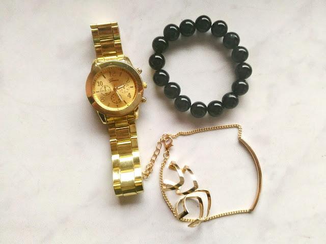 zdjęcie lifestylowe złoty zegarek i biżuteria na marmurkowym tle