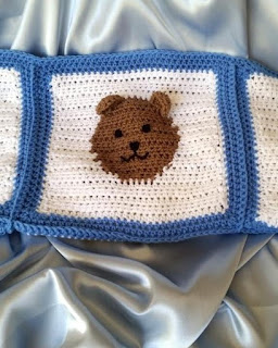 Cool pastel grey blue satin underneath a strip of crocheted fabric, the centerpiece of which is a teddy bear's brown face on a white square with a blue border. The horizontal strip is made of three squares joined together in a row with only the centre one showing in full. The satin can be seen above and below the teddy bear square fabric.