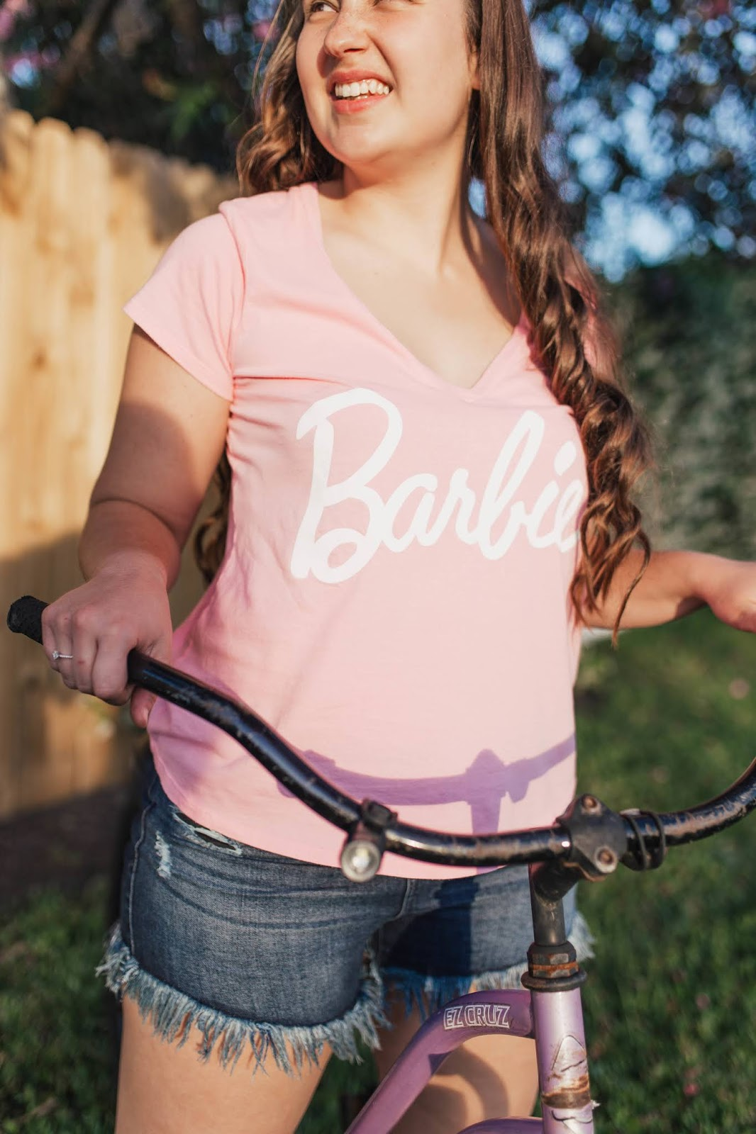 Girl wearing Show Me Your Mumu pink Barbie Collection t shirt with fringe denim shorts