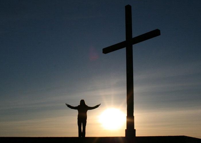 orando aos pes da cruz para Jesus