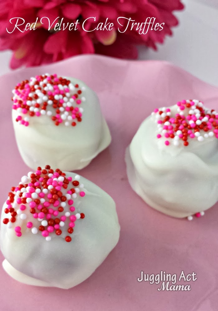 Three Red Velvet Cake Balls covered in white chocolate with pink, red and white nonpareil sprinkles on top sit on a pink fluted plate with fushia flowers in the background.
