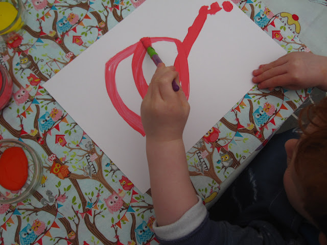 A toddler painting the card with a paint brush