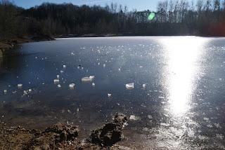 Die Eisfläche der Grube Cox reflektiert die Sonnenstrahlen. Auf der Eisfläche liegen kleinere Eisbrocken.