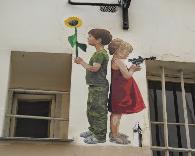 Paris street art graffiti child with gun child with sunflower