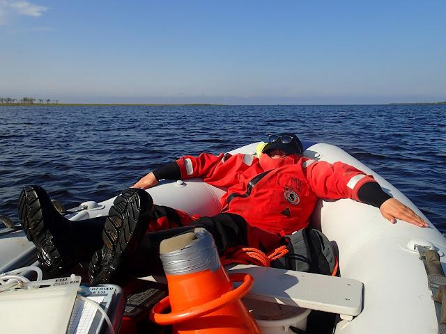 Pelastautumispukuinen henkilö makaa kumiveneen keulassa