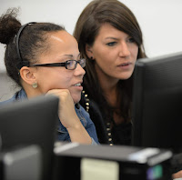 Photo of two students working together on a computer