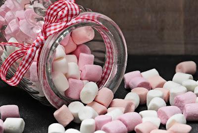 透明な瓶に入った幾つもの白とピンクのマシュマロ