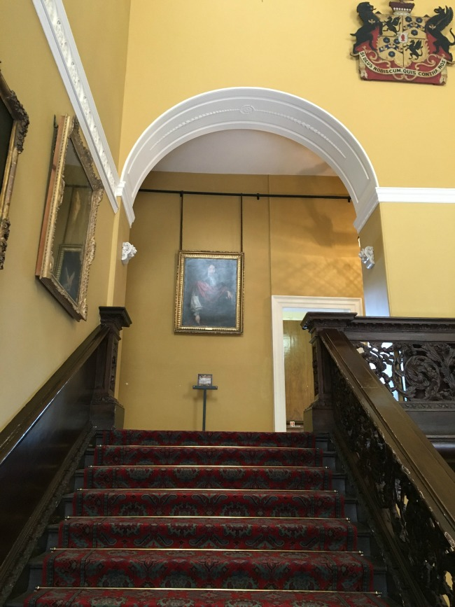 staircase-with-portraits-hung-on-the-yellow-walls