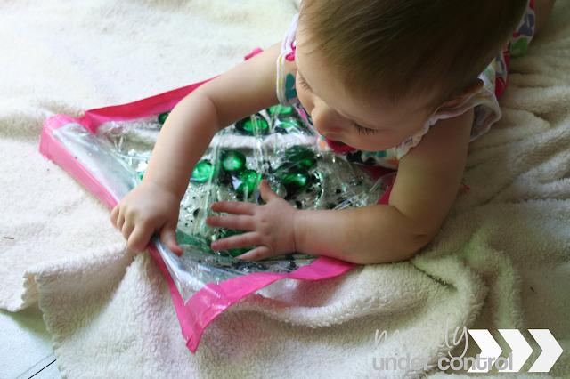 Baby squishing a baby sensory water bag