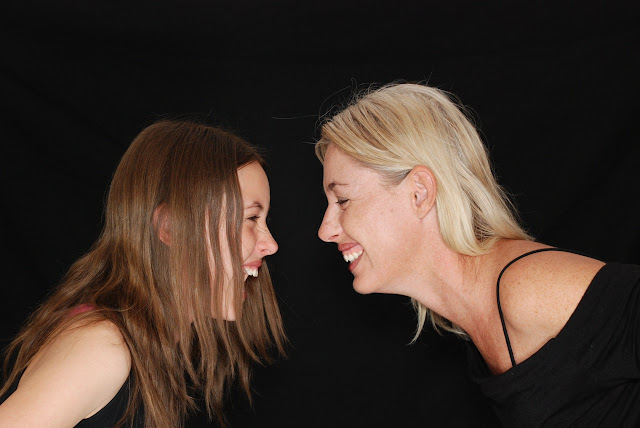 Mom and daughter facing each other, laughing, happy