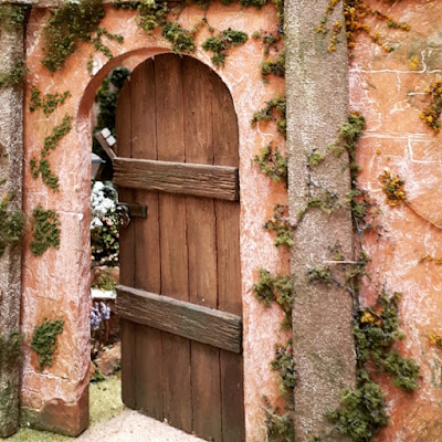 One-twelfth scale miniature door in a garden wall, slightly ajar and showing the garden behind.