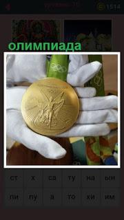 в руках лежит медаль, которую заработал спортсмен на олимпиаде