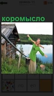 Девушка поднимается от воды по лестнице с коромыслом и два ведра с водой