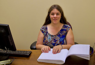 A smiling dark-haired woman at her computer desk, her hands on a page of Braille.