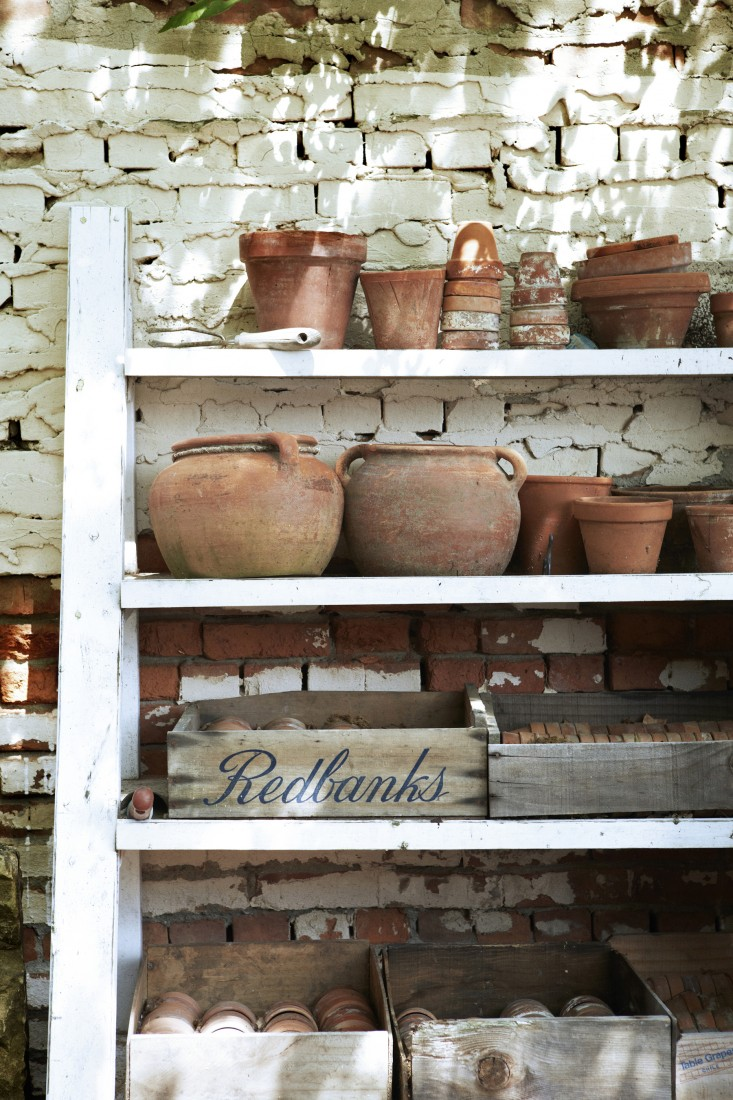 White wood shelves with rustic terracotta pots, vintage boxes, and weathered brick #rusticdecor #europeanstyle #FrenchFarmhouse