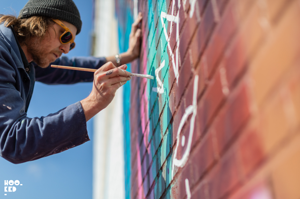 Artist David Walker working with small brushes on his Mural In Ostend