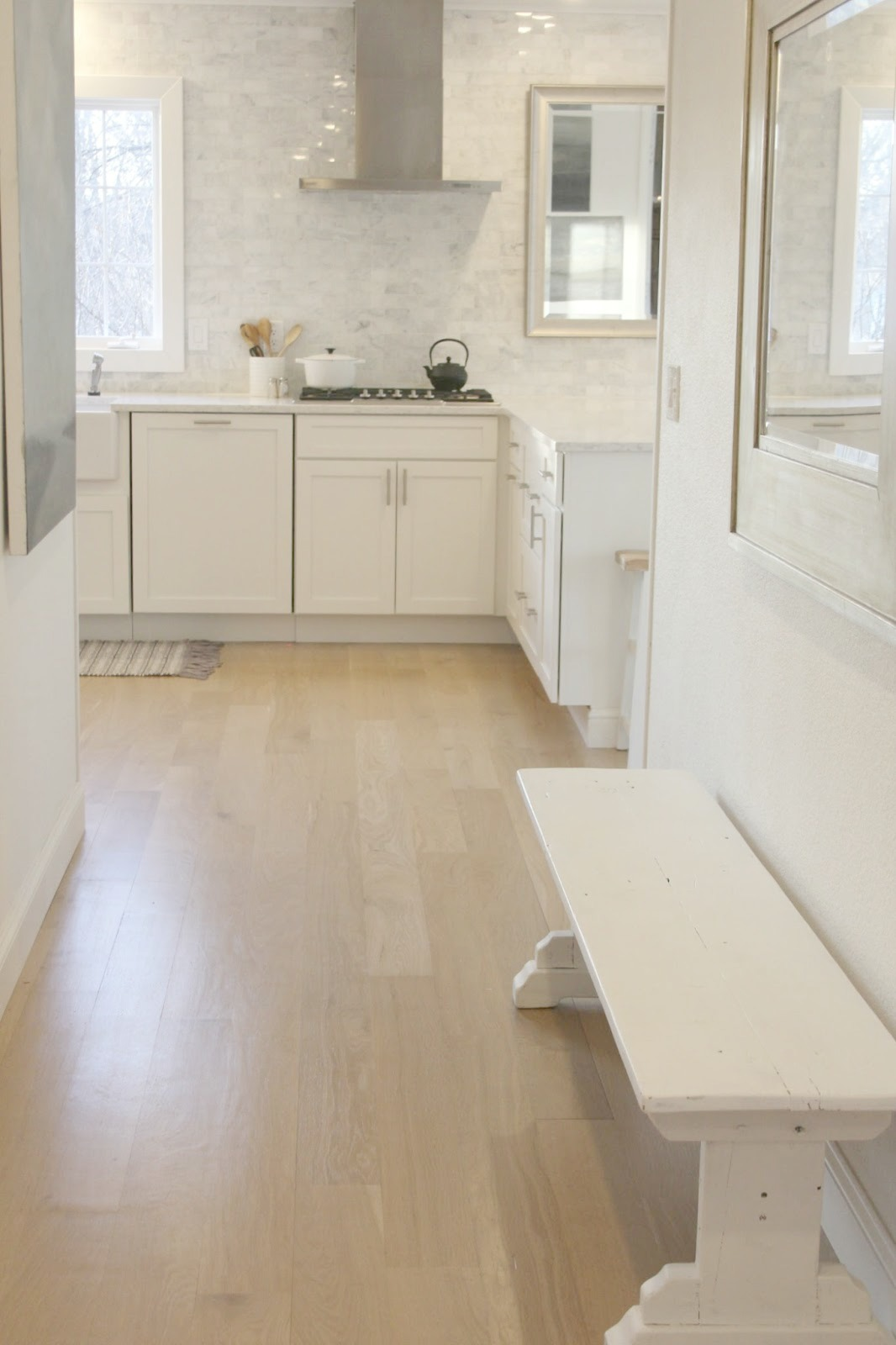Serene white kitchen with modern farmhouse style, white oak hardwood floor, and quartz countertop