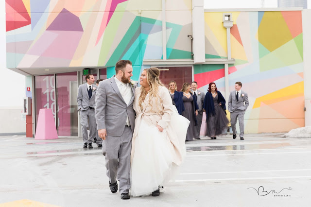 bride and groom on z belt lot rooftop in detroit walking by graffiti