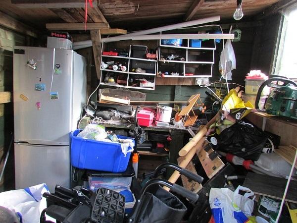 imagem de uma garagem com muitos objetos empilhados, menos o principal: o carro