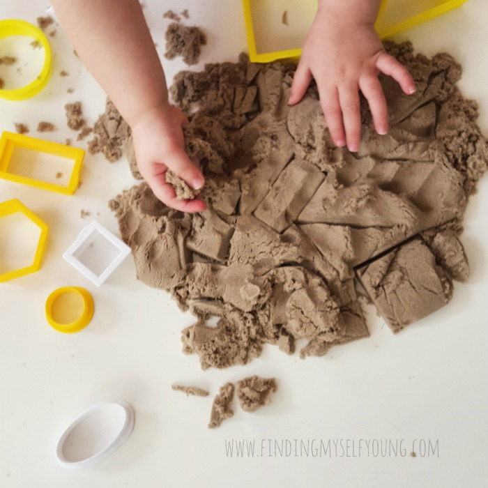 Toddler playing with kinetic sand