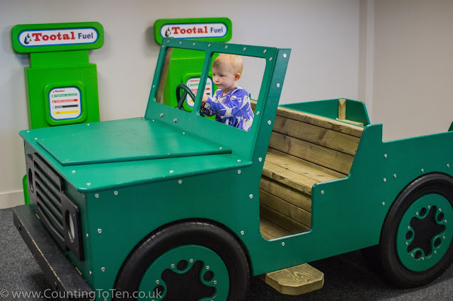 A toddler sitting in a large wooden jeep in front of pretend petrol pumps