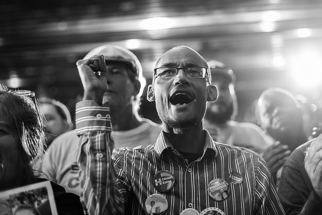 black and white image of a thin man who appears to be white, cheering in the crowd at a Clinton campaign event, his raised fist in the air; his shirt is covered in Clinton-Kaine buttons