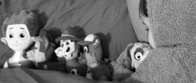 en la cama con todo la patrulla canina, la capucha de un pijama de perrito puesta, solo se le ve el flequillo y las pestañas.