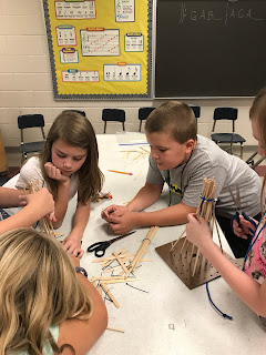 Students sitting at a table working on their windmills