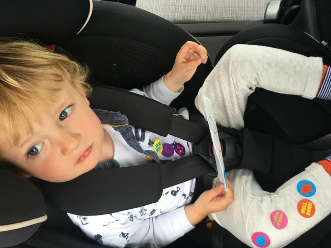 toddler-in-car-seat-with-stickers-on-saying-well-done-good-boy-and-smiley-faces