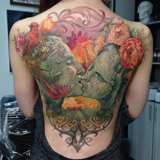 nature themed tattoo with green people kissing surrounded by trees and birds